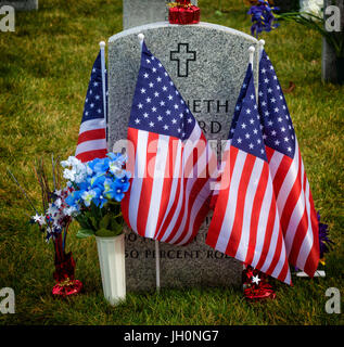 American flagz and  tombstones at an American National Cemetery. - Stock Photo
