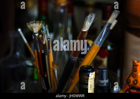 Artist's paint brushes in container on a worktable - Stock Photo