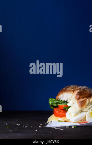 Veggie egg burger with cheese and tomatoes on a countertop, blue background, copy space. - Stock Photo