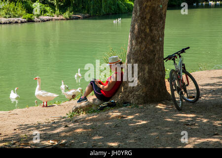Woman taking a rest from a bike ride relaxing on a river bank leaning against a tree and checking her mobile phone - Stock Photo