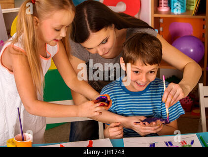 Small students finger painting in art school class. - Stock Photo