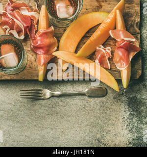 Summer wine party set. Flatlay of Wine snack Prosciutto ham and melon and glasses of rose wine with ice on rustic - Stock Photo