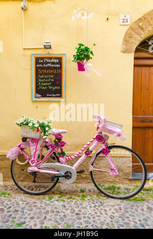 Bicycle Mediterranean, a brightly decorated bike leans against a colourful restaurant wall in the old town quarter - Stock Photo