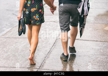 Couple on the street under the rain, woman walking barefoot - Stock Photo