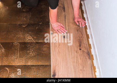 Woman in the laying of plastic laminate or vinyl - Stock Photo