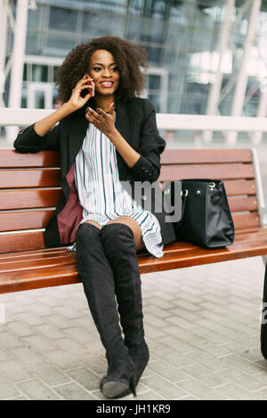 Stylishly dressed smiling afro-american traveler is talking via the mobile phone while sitting on the bench. - Stock Photo