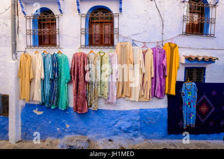 Colourful dresses for sale on an old wall in the Blue City Chefchaouen, Morocco - Stock Photo