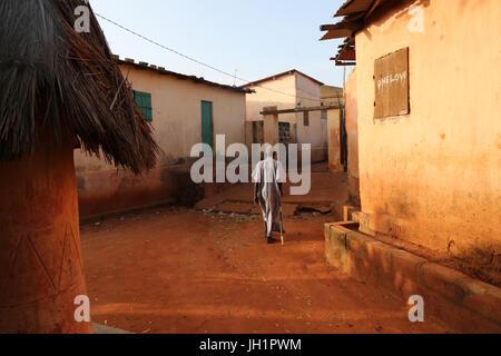 Old man walking in Togoville at sunset.  Togoville. Togo. - Stock Photo