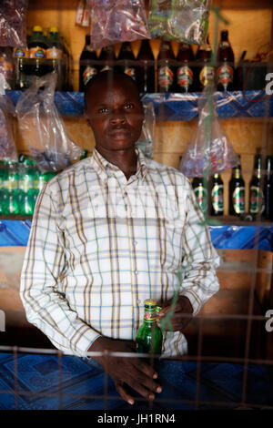 Dennis Openji owns a bar and drink shop in Katulikire. He was able to rent the shop with his first loan from KOLPING - Stock Photo
