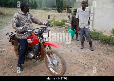 ENCOT microfinance branch manager Francis Buguma visiting farmer client Apollo Byarunga. Uganda. - Stock Photo