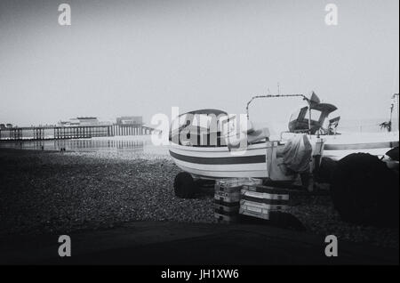 Fishing boats on the beach overlooking a pier. Toned in black and white. A mix of old and new. - Stock Photo