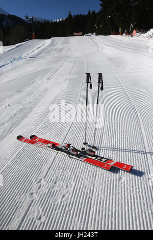French Alps.  Skis and poles stuck in the snow. Groomed Ski Piste. France. - Stock Photo