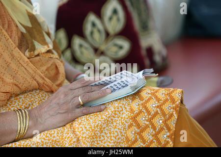 Gurdwara Sahib Silat Road ( Silat Road Sikh Temple ).  Woman reading Sikh holy book. Singapore. - Stock Photo