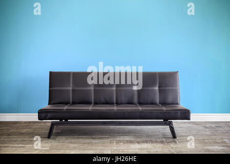 Front view of black leather sofa in interior. - Stock Photo