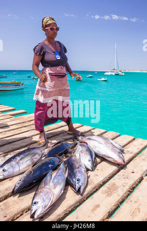Colourful local woman selling freshly caught yellow fin tuna fish from the pier at Santa Maria, Sal island, Cape - Stock Photo