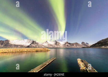 Northern lights on snowy peaks and icy sea along Mefjorden seen from the village of Mefjordvaer, Senja, Troms, Norway - Stock Photo