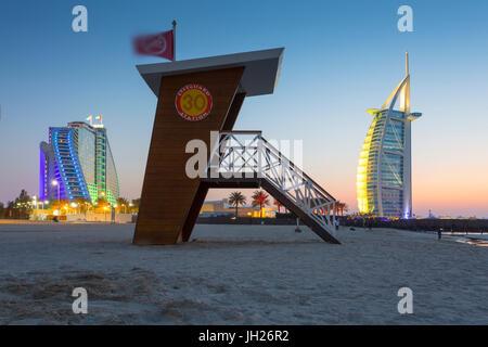 Burj Al Arab Hotel, sunset and lifeguard watchtower on Jumeirah Beach, Dubai, United Arab Emirates, Middle East - Stock Photo
