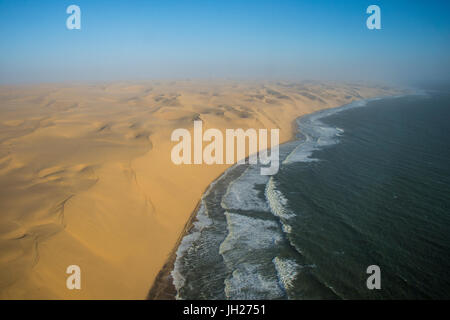 Aerials of sand dunes of the Namib Desert meeting the Atlantic Ocean, Namibia, Africa - Stock Photo