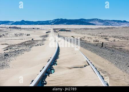 Railway tracks overflown by sand, old diamond ghost town, Kolmanskop, near Luderitz, Namibia, Africa - Stock Photo