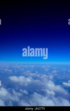 Beautiful view of the clouds below and deep Blue Sky above as seen from an aircraft window - Stock Photo