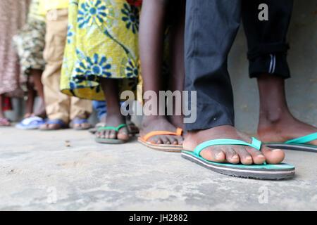 Primary school in Africa. Schoolchildren wearing corlored flip-flops.   Lome. Togo. - Stock Photo