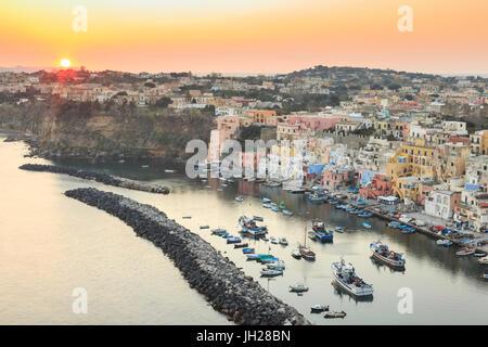 Marina Corricella sunset, fishing village, colourful fishermen's houses, boats and church, Procida Island, Bay of - Stock Photo