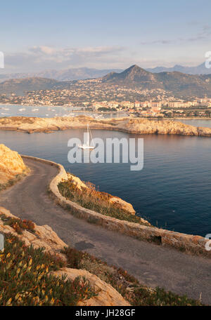 A sail boat in the clear sea around the village of Ile Rousse at sunset, Balagne Region, Corsica, France, Mediterranean, - Stock Photo