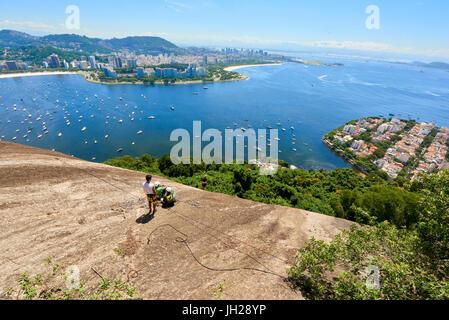 Abseilers in Morro da Urca in Rio de Janeiro with panoramic view in the background, Rio de Janeiro, Brazil, South - Stock Photo