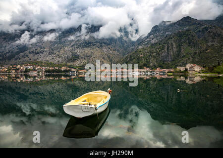 A small fishing boat sits in the reflection of the Old Town (stari grad) of Kotor in Kotor Bay, UNESCO, Montenegro - Stock Photo