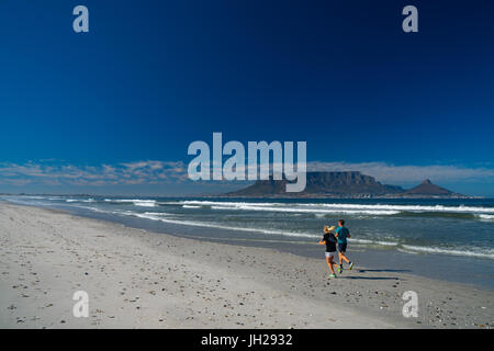 Joggers running on Blouberg Beach in the early morning, with Table Mountain in the background, Cape Town, South - Stock Photo