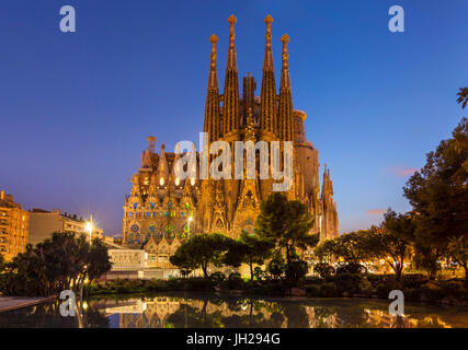 La Sagrada Familia church lit up at night designed by Antoni Gaudi, UNESCO, reflected in pool, Barcelona, Catalonia, - Stock Photo