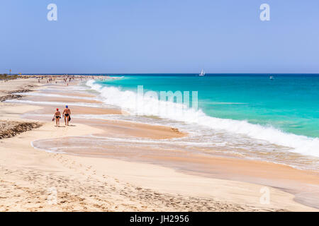 Tourists walking along the sandy beach, Ponta Preta beach, Santa Maria, Sal Island, Cape Verde, Atlantic, Africa - Stock Photo