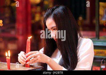 Chua On Lang taoist temple.  Buddhist Worshipper. Candles.  Ho chi Minh City. Vietnam. - Stock Photo