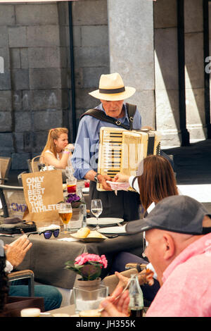 Man in a straw hat playing the piano accordion to people dinning at a restaurant on the Piaza Mayor /  Plaza Mayor - Stock Photo