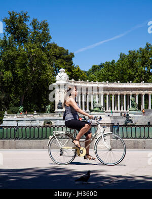 Woman riding a bike in Madrid's Park del Retiro/ Parque del Retiro past the boating lake with the monument to King - Stock Photo