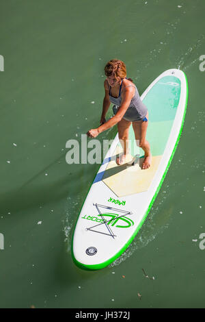 Woman stand up paddle boarding on a river taken from above - Stock Photo