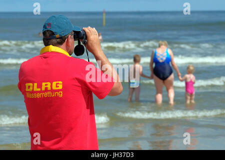 Members of the DLRG German Life Saving Society watch swimmer in the waves of the North Sea on the beach of the island - Stock Photo