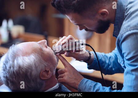 Pleasant hard working barber holding an electric shaver - Stock Photo