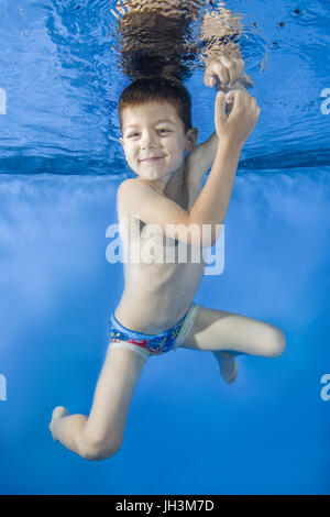 Boy playing under water in swimming pool - Stock Photo
