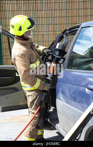 Firefighter training to cut open car - Stock Photo