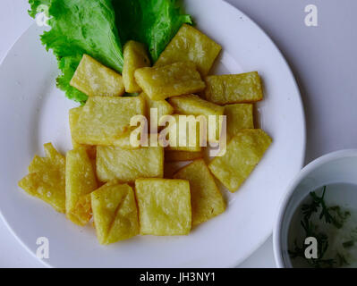 Fried yellow tofu with vegetable on white dish - Chinese cuisine. - Stock Photo