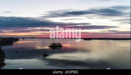 Aerial view of a red sunset at mirroring lake saimaa, in Savonlinna, Savo, Finland - Stock Photo