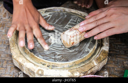 Burmese woman made powder thanaka from ground bark - Stock Photo