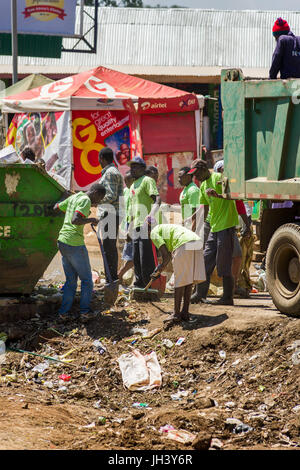 People Clearing Rubbish From Roadside And Skip As Truck Waits To Take Full Bags, Kibera, Nairobi, Kenya - Stock Photo