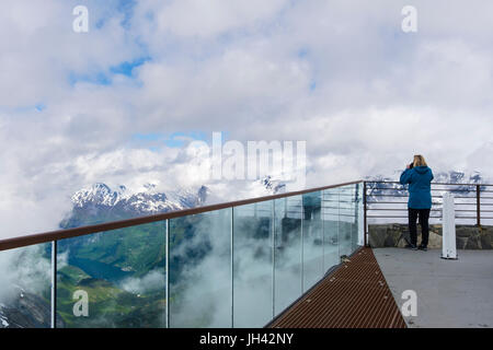 Tourist photographing scenic view from viewing platform on Dalsnibba mountain overlooking Geirangerfjorden. Geiranger - Stock Photo