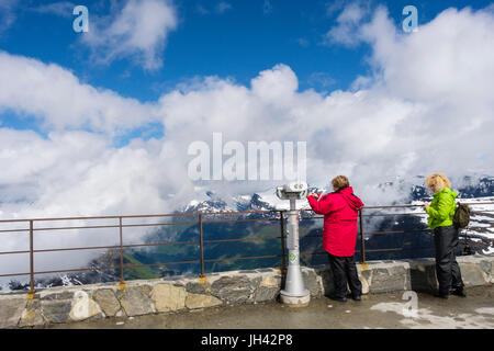 Tourists looking at scenic view from viewing platform on Dalsnibba mountain overlooking Geirangerfjorden. Geiranger - Stock Photo