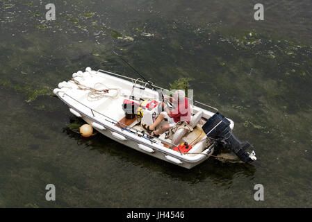 Overview of a man in a boat preparing his rod and line for a fishing trip - Stock Photo