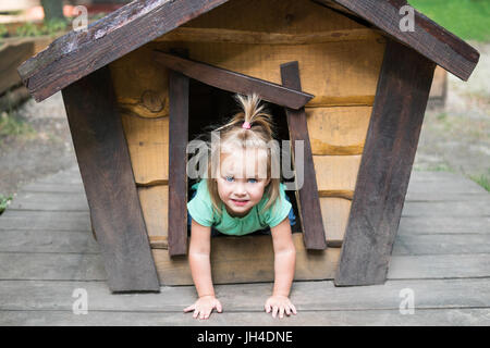 Child in a doghouse - Stock Photo