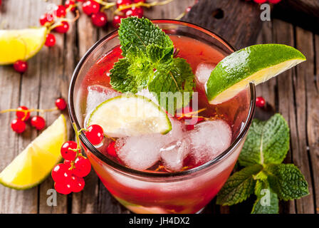 Ideas of summer drinks, dietary healthy cocktails. Mojito from lime, mint and red currant. On the old rustic wooden - Stock Photo