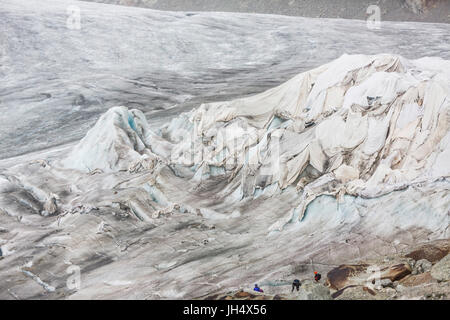 Glacier melt close up: The Rhone glacier is partially squeezed with cloths to slow the melting proc
